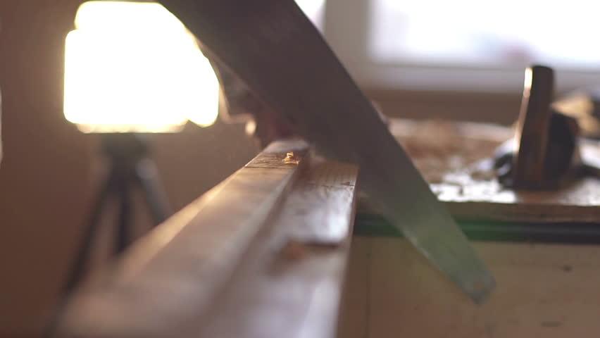 A man sawing wood Board with hand saw. Closeup. Slow motion | Shutterstock HD Video #26101859