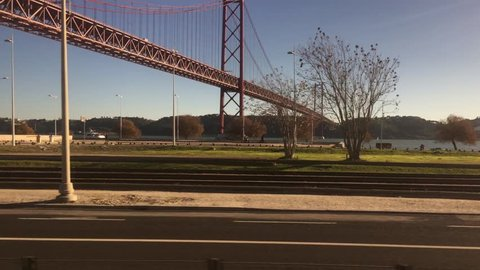 POV Train Ride In City of Lisbon, Window View of Famous Bridge. POV Train ride through city of Lisbon on a beautiful sunny day