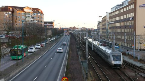 City street and railway track in Helsingborg, Sweden. Traffic and commuter train passing by