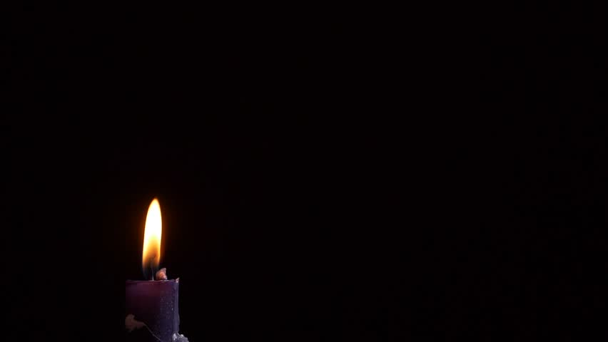 Blowing out of a black candle. Smoke on a black background slow motion