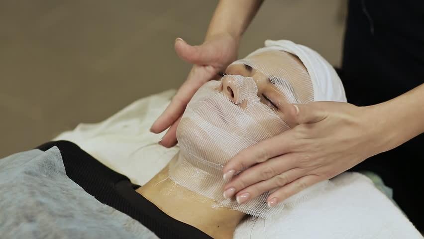 A bandage mask using gauze fabric. Adjustment of gauze tissue around the neck of a girl with cream.