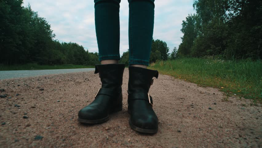 Young pretty caucasian blue eyed abused blonde girl in leather jacket with big bag with scar on face walking distractedly at side of country road on early summer morning