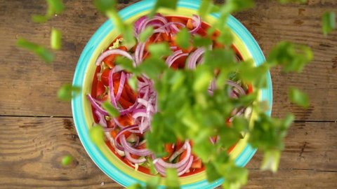 falling cut green onion in dish with salad, slow motion 250 fps, above view
