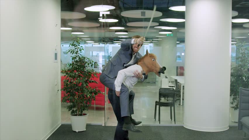 Funny scene with a positive office worker with a horse's head mask carries on his back a colleague with a katana