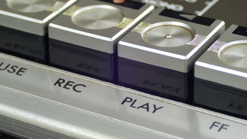 Pushing Record Button on a Vintage Tape Recorder. Close-up. Pushing a Finger Button Record. Man finger presses playback control buttons on audio cassette player.