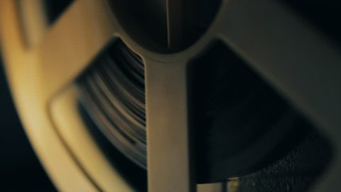 Old 8mm film projector playing in the night. Close-up of a reel with a film. 4k