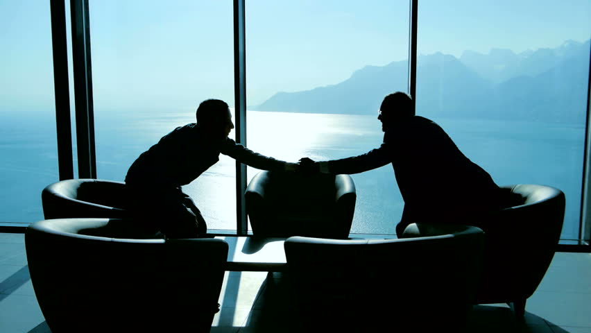 lobbyist handshaking with partner after business deal agreement. businessman meeting in modern lobby talking together. two people having a conversation about financial strategy