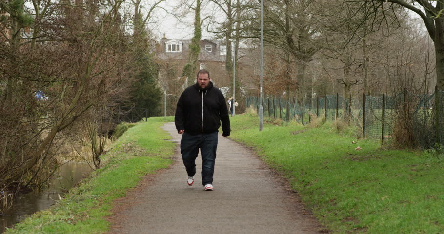 4K Unhappy overweight man walking towards camera, alone outdoors in the park. Social issues & unhealthy lifestyle concept. Slow motion.