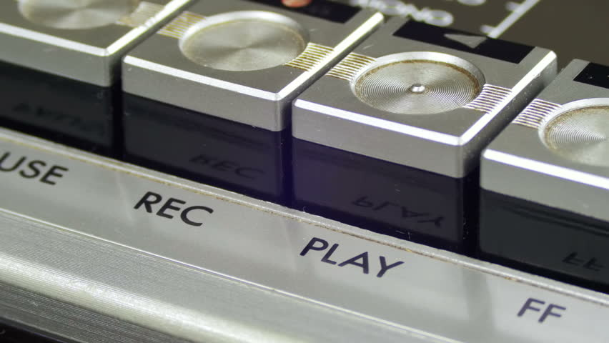 Pushing Play Button on a Vintage Tape Recorder. Close-up. Pushing a Finger Button Play. Man finger presses playback control buttons on audio cassette player.
