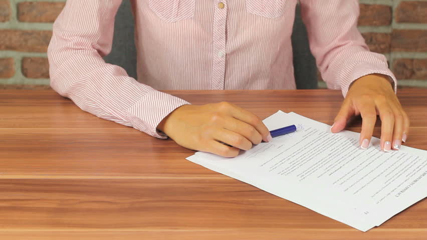 Woman Signing contracts - putting her signature on a document using a fountain pen