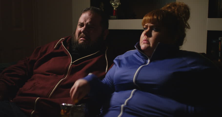 4K Funny couch potato couple eating junk food in front of the TV & reacting with horror
