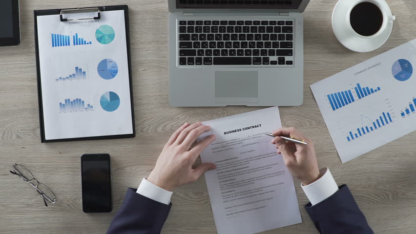 Head of department reading business contract attentively, top view of workplace   Shutterstock HD Video #26230082