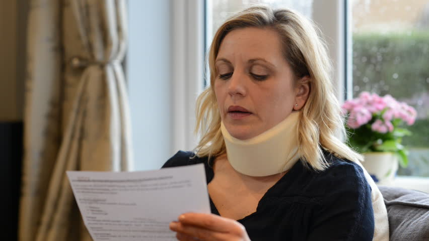 Mature woman at home wearing neck brace reads letter in respect of compensation for her injury - she winces in pain