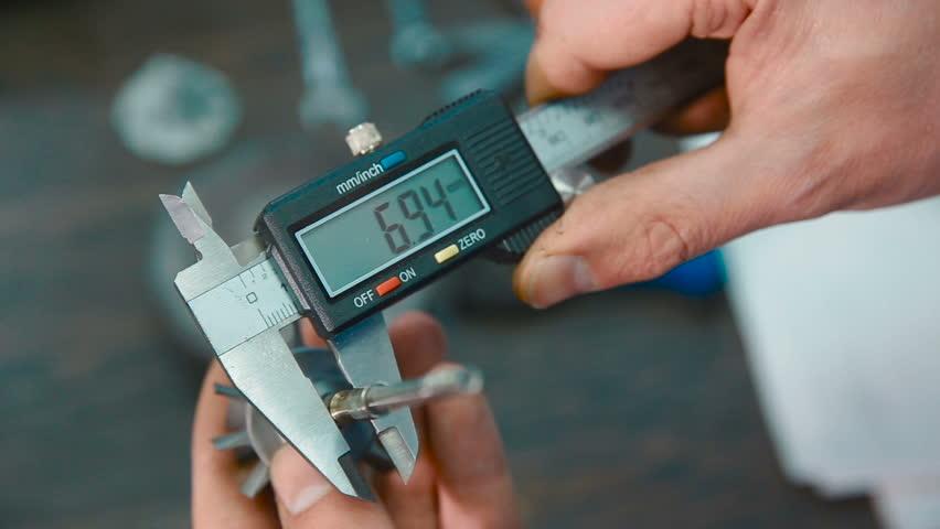 Industrial worker measure detail with digital caliper