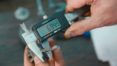 Industrial worker measure detail with digital caliper