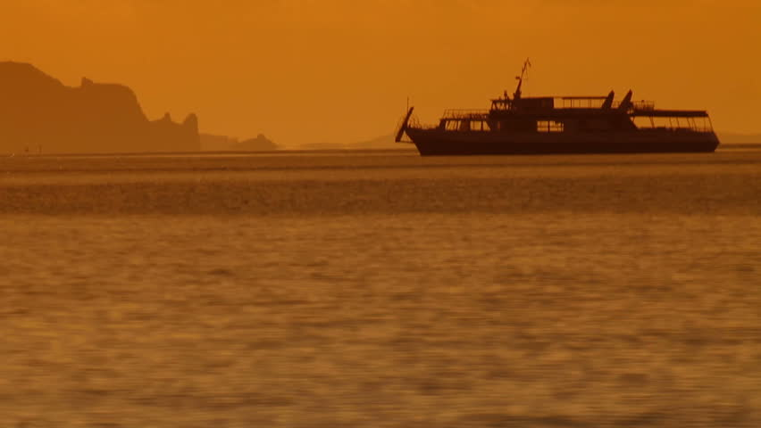 Silhouette of tourist cruiser at sunset