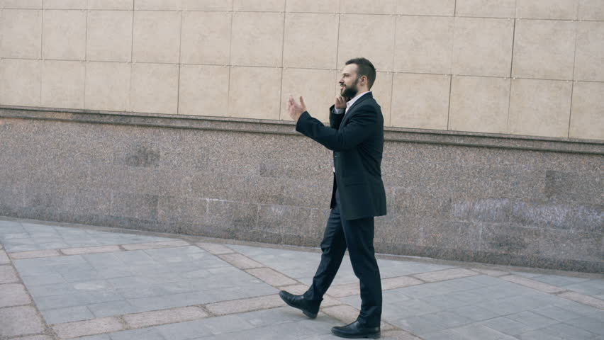 Dolly shot of young bearded business man talking at smartphone and feels happy about making deal walks near office buildings #26254259