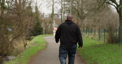 4k, Overweight man walking on the trail in a park. Rear view.