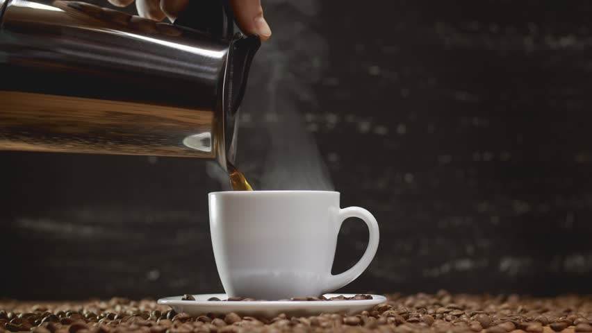 Pouring coffee from coffee pot in white cup surrounded by coffee beans on dark background with copyspace. 4k UHD