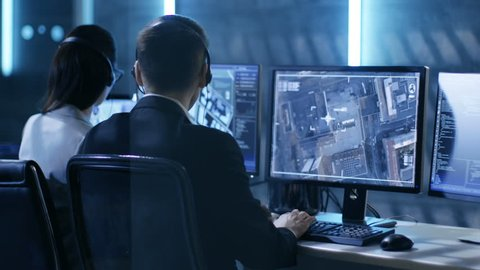 In Government Agency System Surveillance Center Employees Trace Criminal with Help of GPS. Room is Full of Displays with Various Data on Them. Shot on RED EPIC-W 8K Helium Cinema Camera.