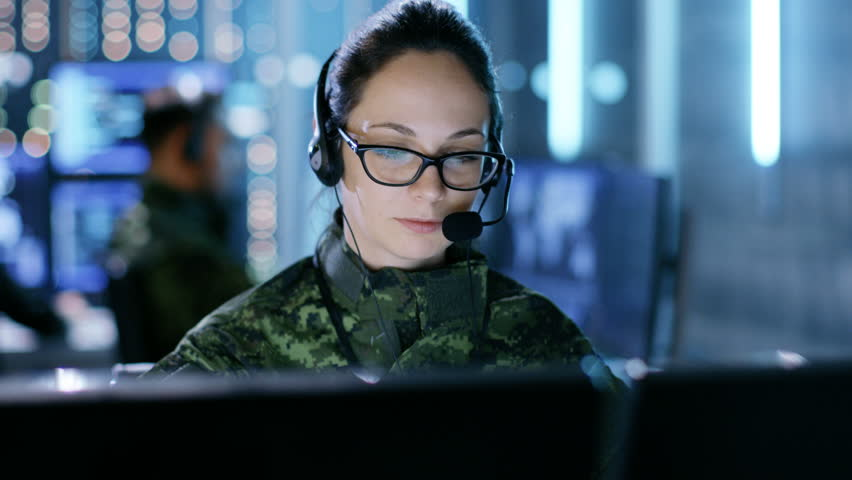 Female Military Technical Support Professional Gives Instructions into Headset. She's in a Monitoring Room with Other Officers and Many Working Displays. Shot on RED EPIC-W 8K Helium Cinema Camera.