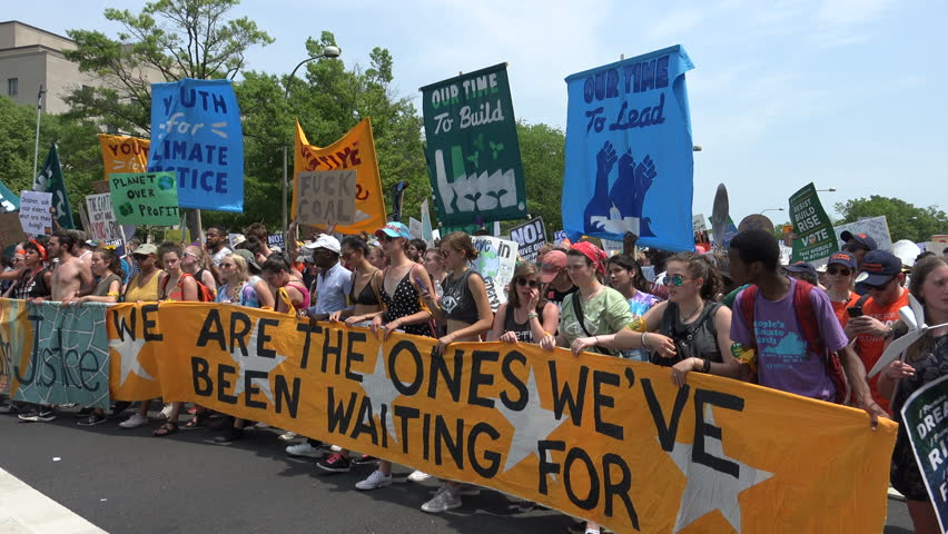 "WASHINGTON, DC – APR. 29, 2017: ""No Peace, No Justice,"" People's Climate March massive crowd protesting  Donald Trump's environmental protection rollbacks, march on Pennsylvania Ave.to White House."