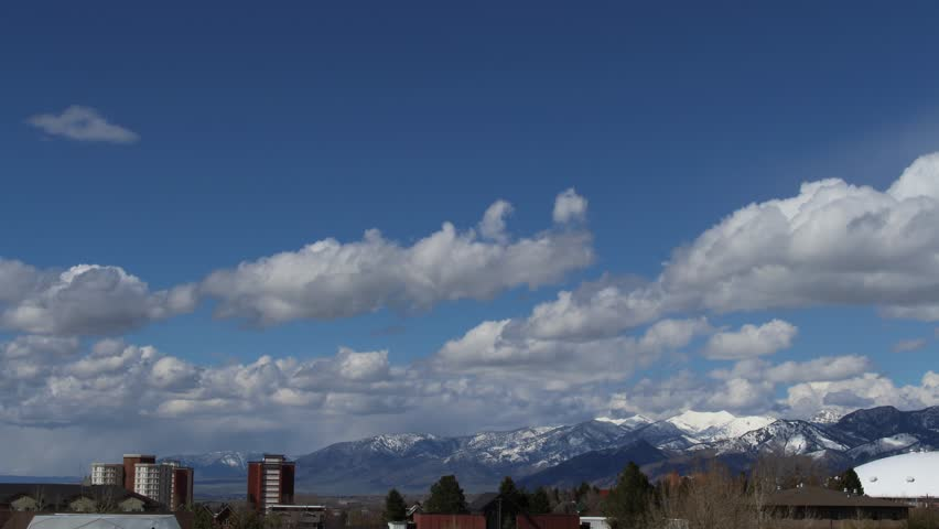 Time lapse of Clouds Over a Small Town and Snowy Mountains