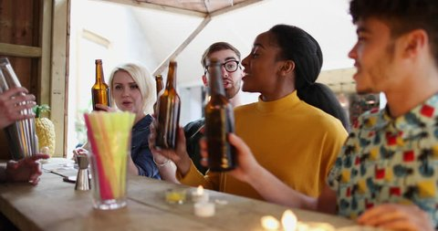 Group of friends at a street food bar saying cheers with beer