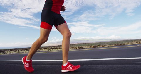 Running shoes on man triathlete runner - close up of feet running on road. Male athlete jogging outside exercising training for triathlon ironman. SLOW MOTION RED EPIC.