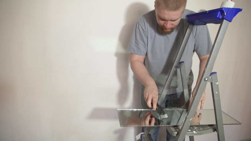The glazier cuts a mirror lying on the stairs using a glass cutter. A man in jeans and a blue T-shirt is working in a room with a white wall.