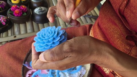 Thai craftswoman carves a lotus flower from blue soap.