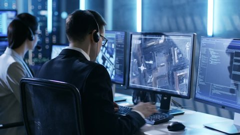 In Government Agency System Surveillance Center Employees Trace Criminal with Help of GPS. Their Room is Full of Displays with Various Data on Them. Shot on RED EPIC-W 8K Helium Cinema Camera.