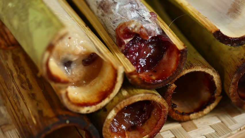 Burned sticky rice with sweet coconut milk in bamboo shot. Khao Lam is Thai dessert, selective focus.   Shutterstock HD Video #26404409