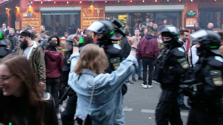 "Berlin, germany - may 01, 2017: Girl showing middle finger to riot police during the ""Revolutionary May 1st Demonstration"" on labor day in Berlin, Kreuzberg."