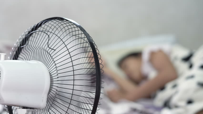 Little girl sleeping with fan blowing
