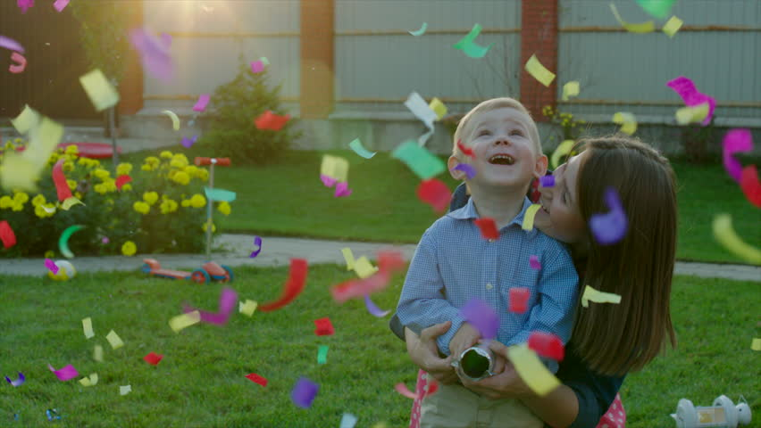 Mom And Son Exploding Party Cracker Watching Confetti At Sunset