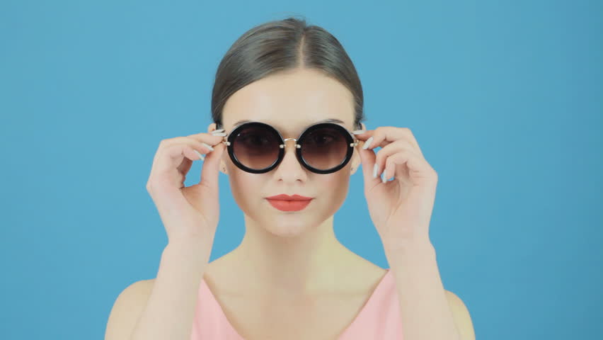 Fashional Portrait of Brunette Model Wearing Cool Sunglasses and Pink Dress on Blue Background. Perfect Girl is Posing in Studio.