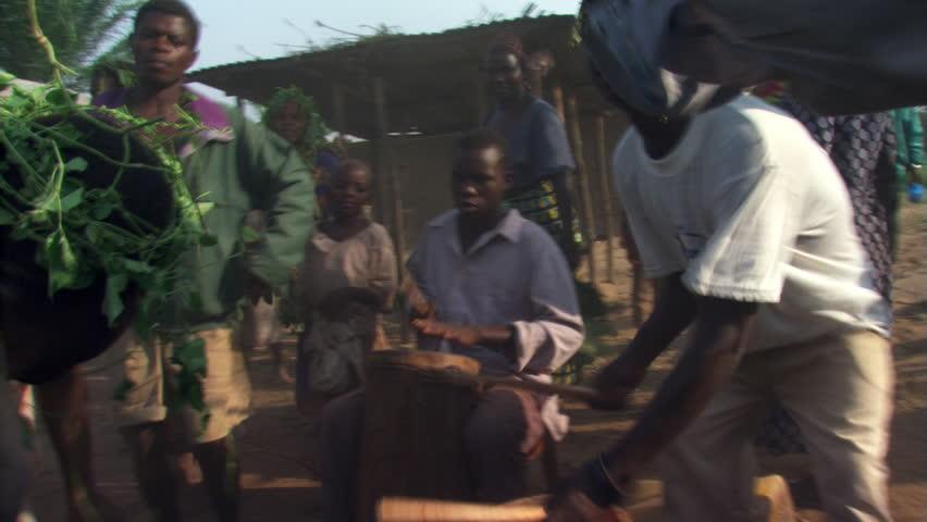 Drummers surrounded by dancers and watching children in Bundibugyo, Uganda