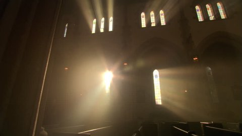 Priest walking down the aisle in darkened nave of Catholic church
