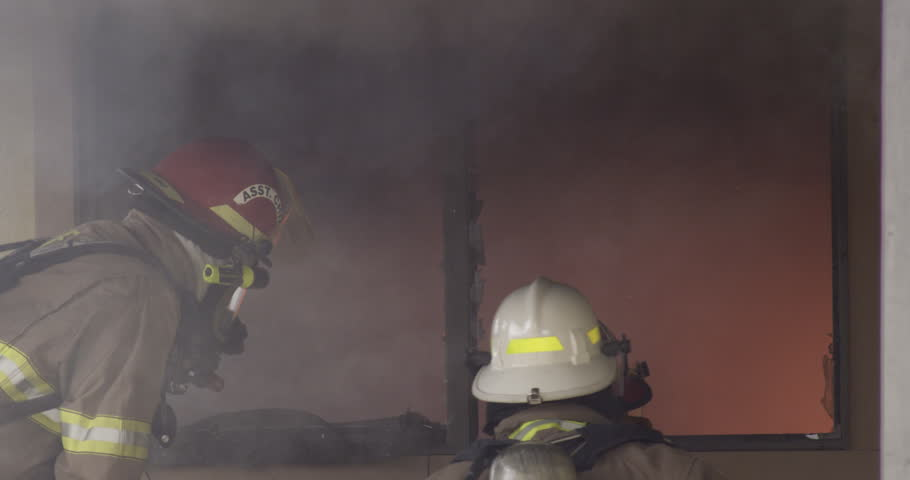 Three firefighters in front of a glowing window spray a stream of water into the room   Shutterstock HD Video #26509289