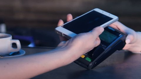 Female paying through smart phone using NFC technology. Close-up. 4K.