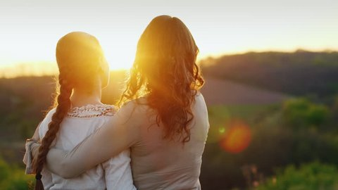 Mom gently kisses her daughter's temple. Together they admire the beautiful sunset. Back view
