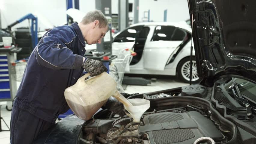 Tilt down of beautiful woman in mechanic uniform walking for Garage europe auto center fresnes