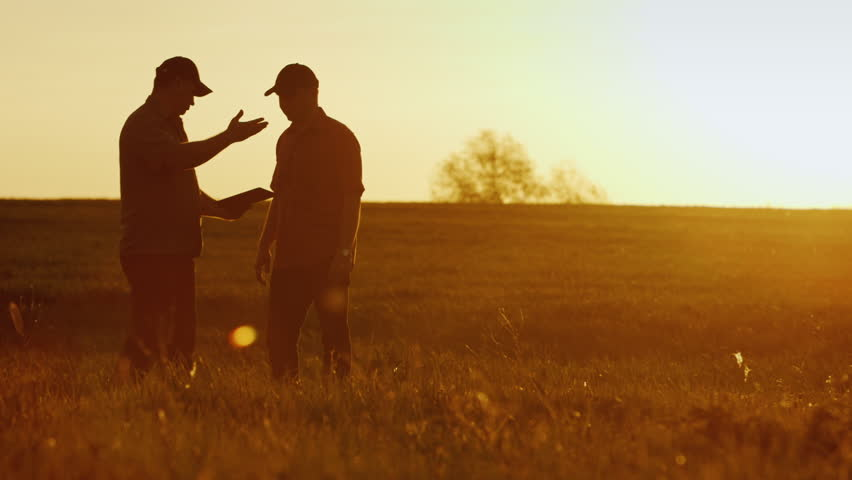 Two businessman farmers shake hands with each other firmly. They talk on the field against a beautiful sunset, they use a tablet. Deal