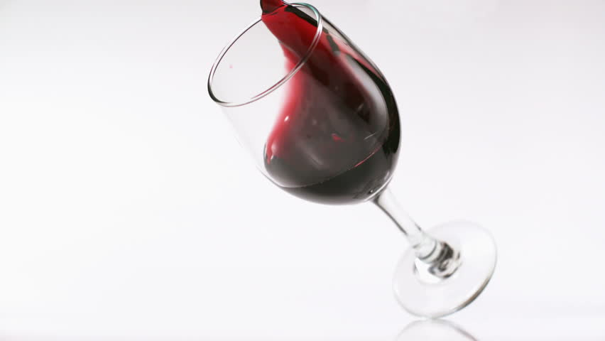 Glass of red wine falling and wine spilling over shooting with high speed camera, phantom flex.