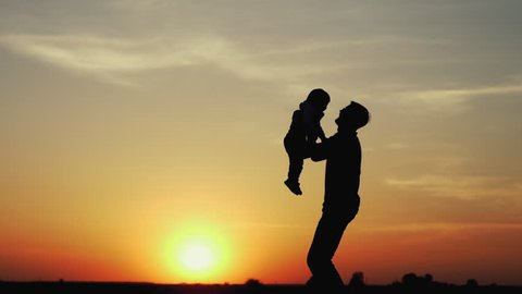 Happy child rushes into hands of father. Family hugs over sunset sky background. Silhouettes of anonymous boy and man outside in summer or autumn landscape. Slow motion 180fps