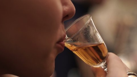 Girl drinks whiskey from a small glass in a bar. Blonde girl tasting cognac in bar. Close-up of a girl drinking rum in a bar at a party