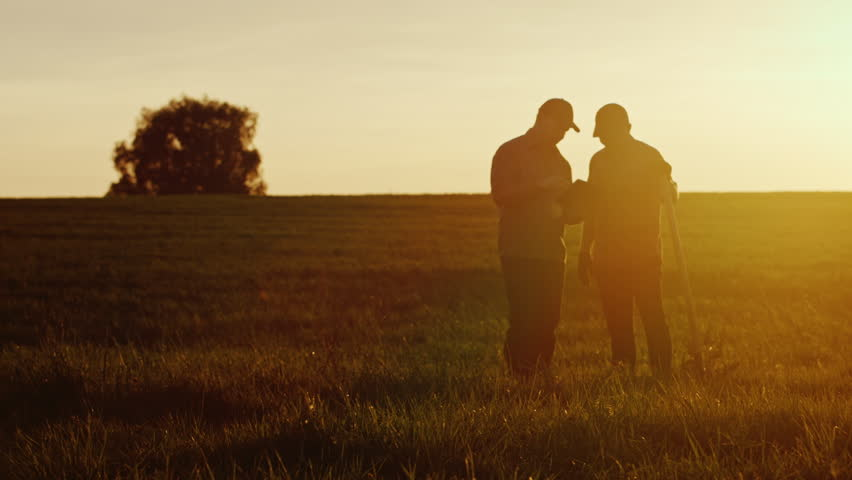 Two American farmers communicate in the field at sunset. Next to them is a shovel
