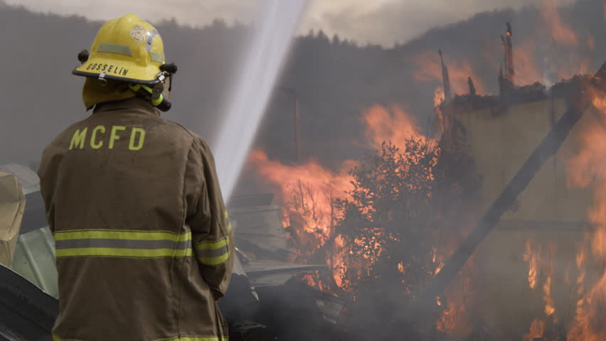 Fireman shoots a powerful stream of water onto a raging structure fire