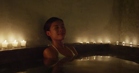 Relaxation and luxury at spa jacuzzi hot tub resort. Woman taking a bath at night by candlelights outside
